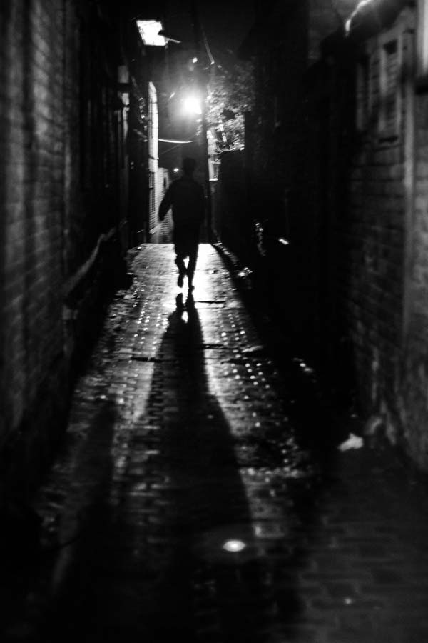 A boy leaves behind shadow while passing through alley in city