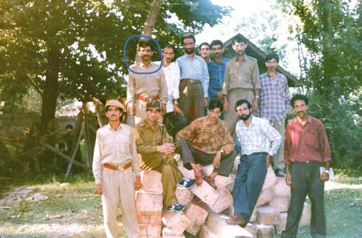 Abdul Rehman Ganie (encircled ) standing with other colleagues  over the seized timber.