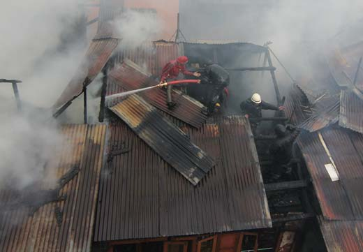 Fire fighters dousing the flames on the roof  of residential  house in Srinagar.