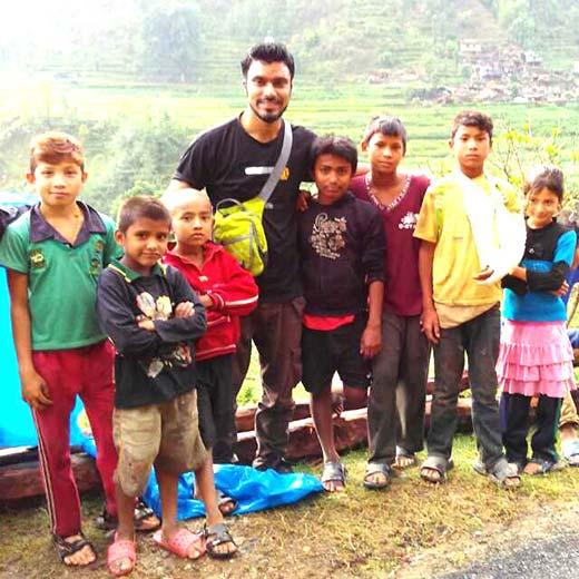 Er Abdul Wajid  standing with children of quake hit Nepal.