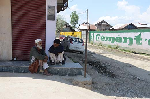 Two elders  busy conversing on a shop front in Sopore town.