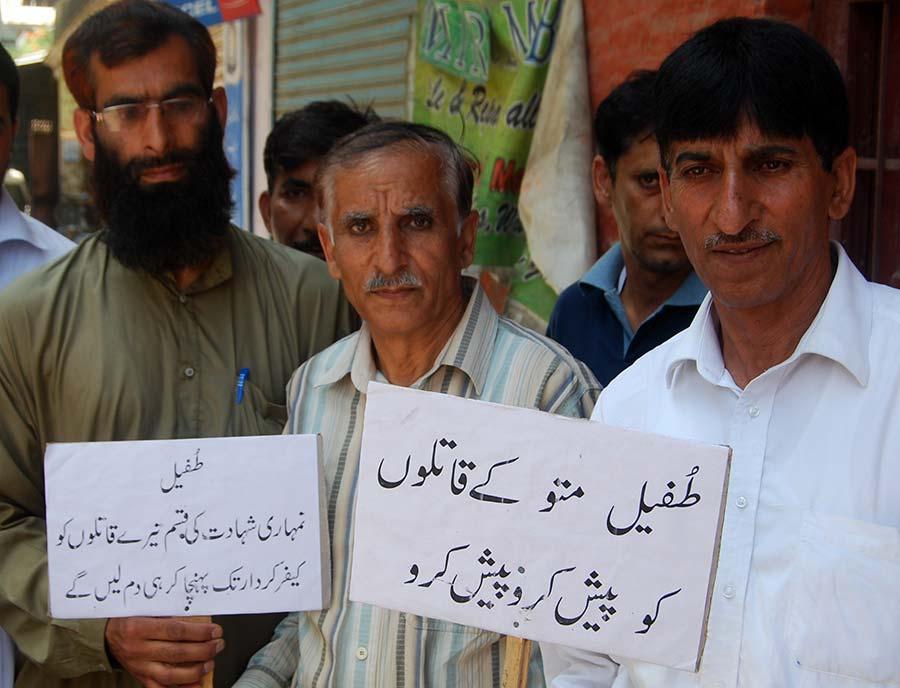 Muhammad Ashraf, Tufail's father holding a placard.