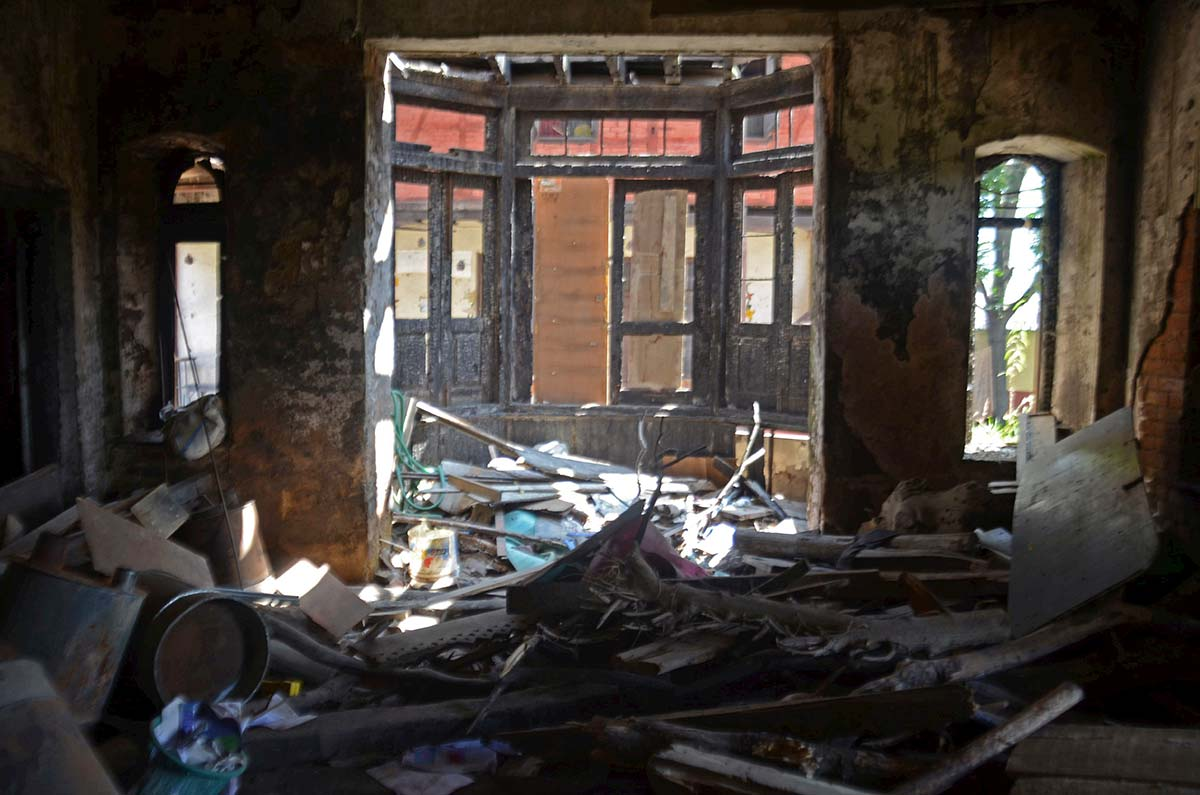 Charred walls and debris inside gutted Red 16 building.
