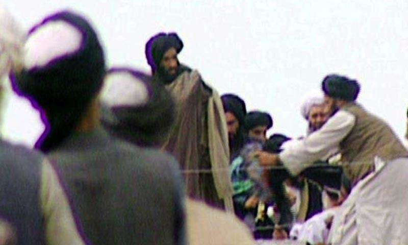 Mulla Omar waering Prophet's cloak.